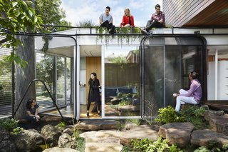 The roof garden, lush with edible plantings, is accessible by ladder.