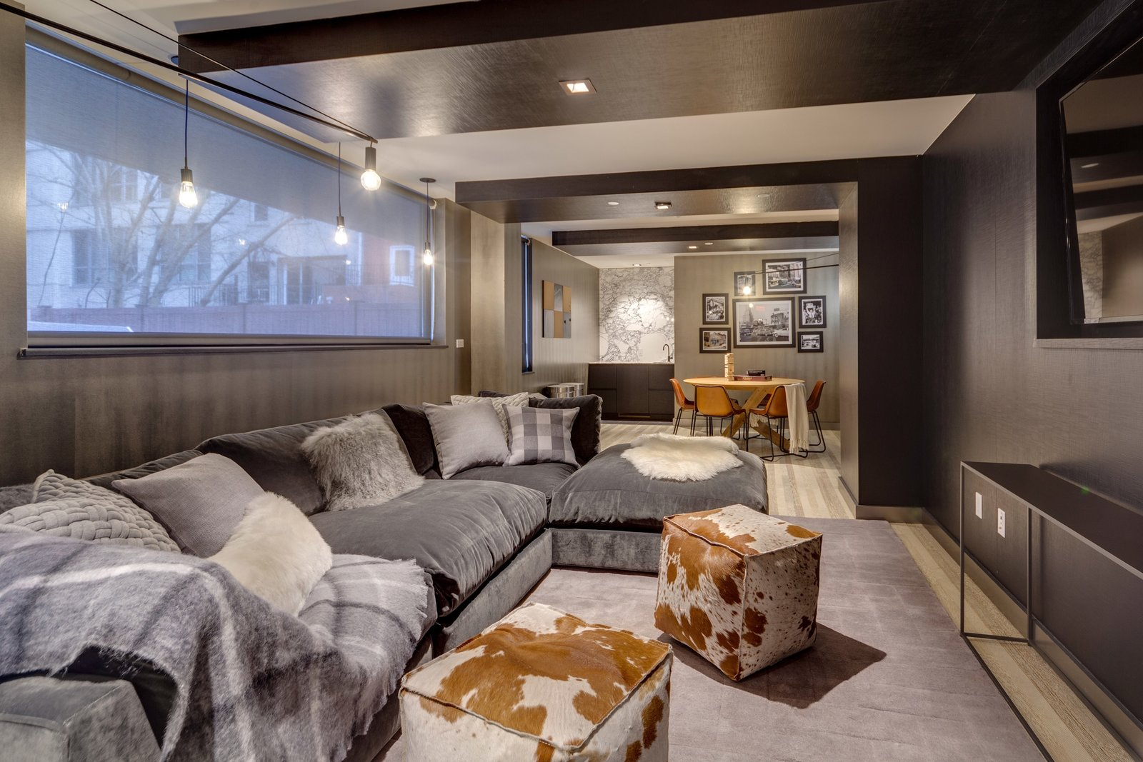 Living Room, Light Hardwood Floor, Console Tables, Chair, Table, Sectional, Ottomans, Wall Lighting, Rug Floor, and Recessed Lighting The media and game room acts as the social hub for The Baltic residence.  Photo 4 of 12 in These 3 Co-Living Companies Are Transforming Urban Living