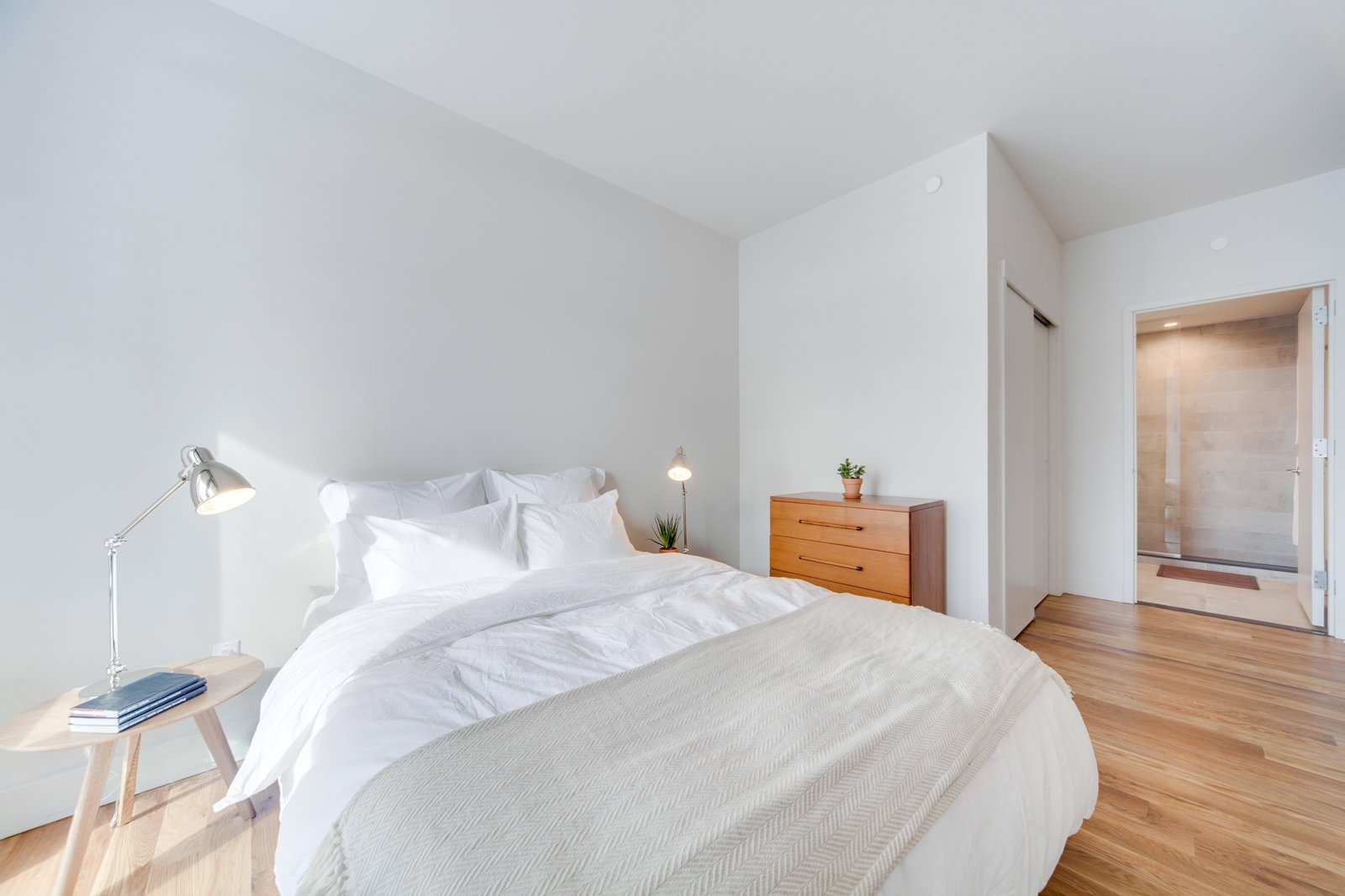 Bedroom, Medium Hardwood Floor, Table Lighting, Bed, Night Stands, and Dresser In the Baltic residence, renters can choose from a private studio or a co-living suite with several private bedrooms and a common space.  Photo 3 of 12 in These 3 Co-Living Companies Are Transforming Urban Living