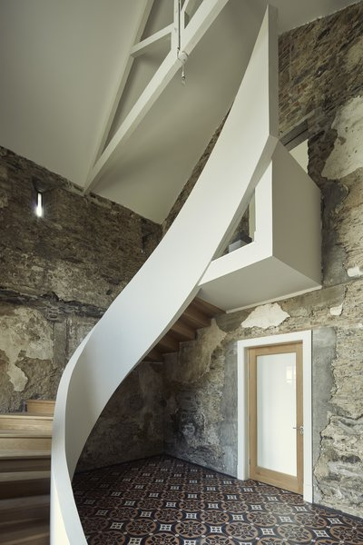 """Concrete ribbon stairs"" with timber cantilevered steps have been inserted to create a modern contrast to the building's original un-plastered walls. The staircase has been designed so that it didn't touch the exterior wall."