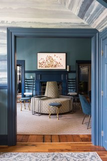 """Off the foyer, what was originally the check-in area for guests was turned into a swanky lounge, featuring a round """"sociable sofa,"""" upholstered in Kravet Verbier Diamond fabric in Leaf/Teal."""