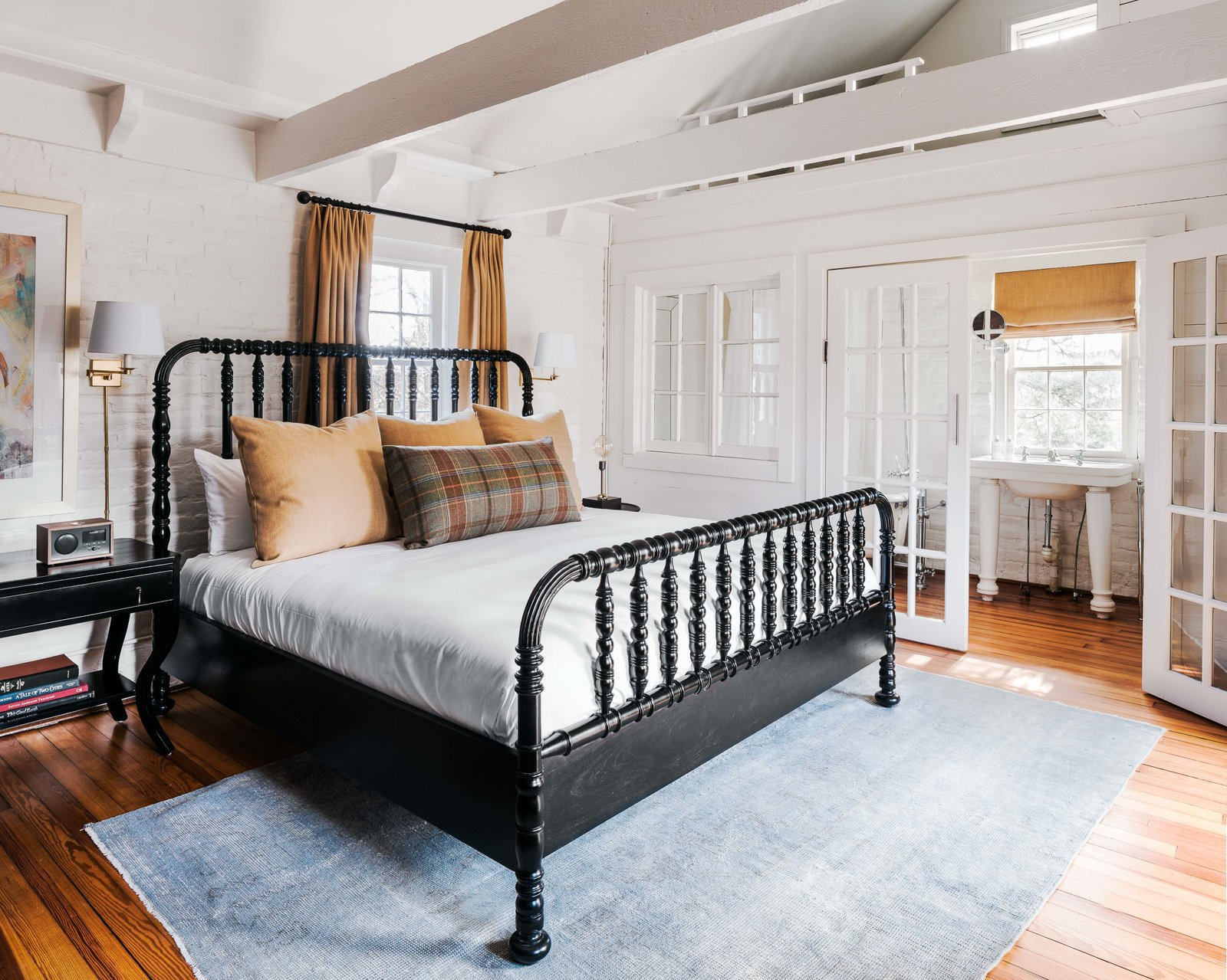 Bedroom, Wall Lighting, Night Stands, Bed, Medium Hardwood Floor, and Rug Floor Inside the cottage are two bedrooms that have been updated with crisp white paint, new linens, and light fixtures.  Photo 14 of 17 in The Clifton by Dwell from An 18th-Century Virginian Hotel Boasts an Elegant New Look