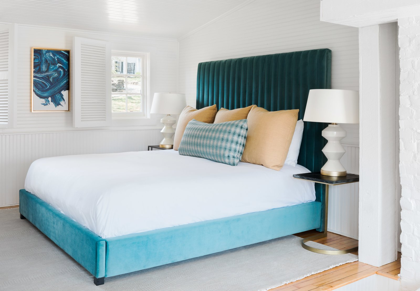 Bedroom, Bed, Night Stands, Table Lighting, Medium Hardwood Floor, and Rug Floor Guest suites in the livery include cozy living areas and king-size beds that are upholstered in a rich turquoise velvet.  Photo 16 of 17 in An 18th-Century Virginian Hotel Boasts an Elegant New Look