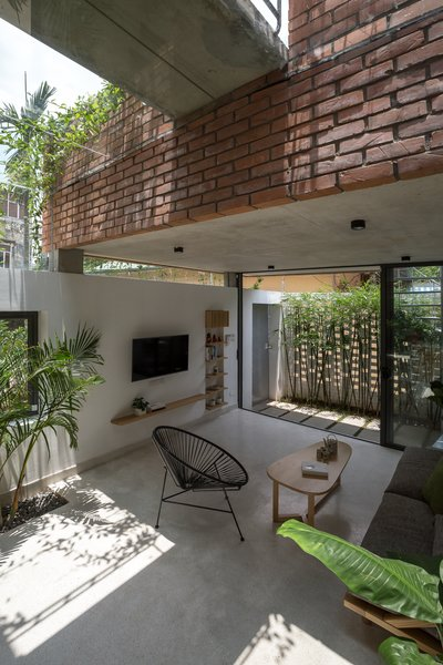 Inside the home, concrete floors, white walls, and plenty of windows keep the living spaces feeling bright and cheery.