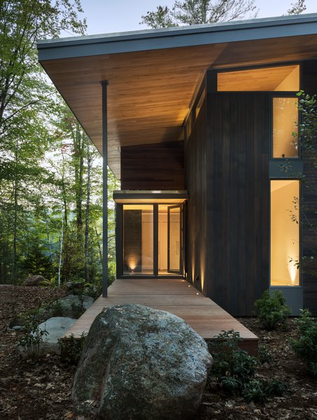 The exterior palette consists of dark cedar siding, mahogany decks, and exposed gray steel beams.