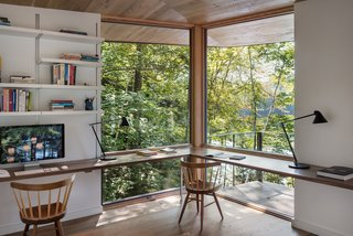 In the study of this stunning, modern cabin by Murdough Design, corner windows give the home office a tree house feel with views of the lush surrounding canopy and lake.