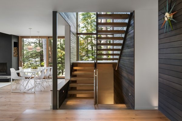 The exterior's dark cedar siding was extended into the stairwell to connect the indoors and outdoors.