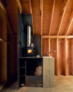 Inside, a Cubic Mini wood stove warms the cozy 8' x 12' space.