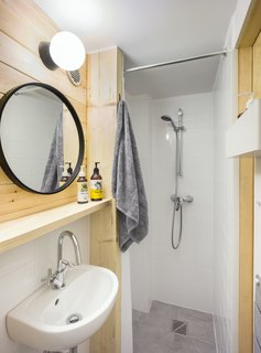 For a clean and minimal aesthetic, white and gray tiles are paired with pine wood in the bathroom.