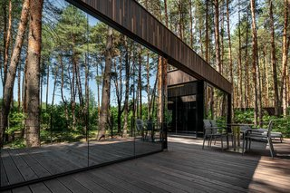 Nestled within Verholy Relax Park in Sosnivka, Ukraine, these contemporary guest cottages by YOD Design Lab offer a sense of solitude and a meaningful outdoor connection. Highly reflective windows mirror the forest, while an outdoor terrace wraps around each cottage. Inside, interiors are swathed in organic hues and materials to allow the views to be the focal point—each dwelling is arranged so that windows peer at pines rather than another building. The houses are even installed on geo-screens to save the root systems of the surrounding trees in the forest, to prevent them from being cut down.