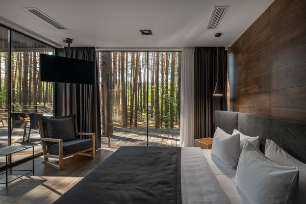 In the bedroom, a gray cotton upholstered headboard grounds the bed, and veneered oak plywood walls serve as a backdrop.