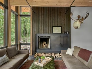 The fireplace is set within a custom blackened steel enclosure with a charred cedar backdrop.