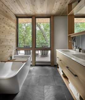 Off the master bedroom and bath, a large deck provides expansive views of the forest.