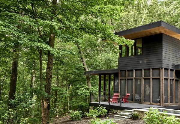 """The exterior combines charred cedar siding, cedar beams, and black cement board siding. """"Black may seem like an extreme choice sometimes,"""" says Howe. """"It would be hard to imagine any other color though. It sits lovely in the woods. It falls into the shadows in the summer, under the canopy, and it blends with the dark tree trunks in the winter."""""""