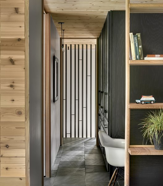A partition wraps the stairway from the basement to the third-floor master suite. Its form was inspired by the way light filters through the trees in the forest.