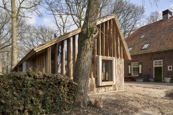 Annemariken and Geert sourced old oak trees from their estate to build a barn that provides space for storage, working, and a car port.