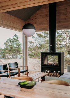 A cozy Bodart & Gonay tunnel stove heats the main living area. A black-and-white String pendant light by Flos adds contrast to the wood-clad room.
