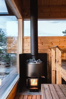 A traditional Finnish wood stove by Kota Luosto heats not just the sauna, but the running water and floors throughout the cabins.