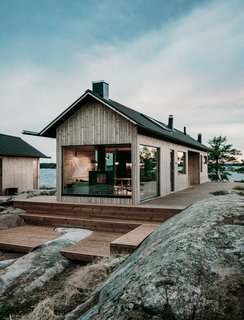 The exteriors of the cabins are clad in Lunawood pine, and the roofs are covered in felt for a matte appearance.