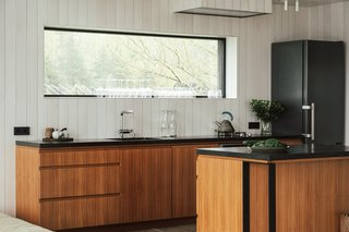 Kitchen cabinetry is finished with teak veneer and topped with black concrete.