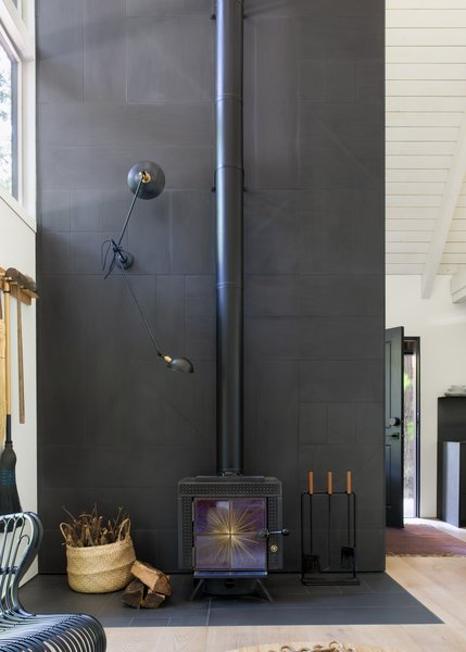 In the all-white space, the architects defined gathering places with the use of black tones. In the living room, they created a fireplace surround by cutting and arranging 2' x 4' tile into a geometric quilt pattern.