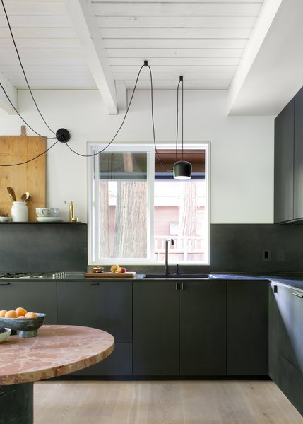 "Black appliances and fixtures blend seamlessly into the cabinetry. The lack of a large fridge helps give the kitchen its streamlined and minimal appearance. The couple carefully integrated appliances to make the small space fully functional for entertaining. Two CoolDrawers are tucked under the counter to chill wine and store enough food for the weekend. Two ovens allow home cooks to bake bread and roast meat simultaneously. ""It just works really well for us,"" says Daniel. ""Our counter space is at a premium, and we just didn't need a giant refrigerator. This way, we can have the L-shaped counter. That was a very strategic decision—it doesn't need to be more than what it is."""