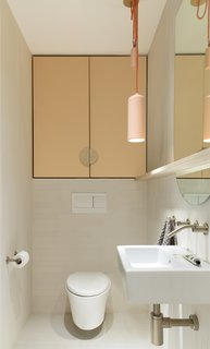Above the Kohler toilet hangs a custom cabinet by Barrett Karber. The contemporary mirror and shelf were also made by the furniture designer.