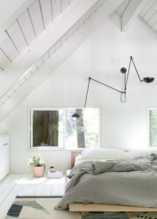The lofted bedroom is outfitted with soothing textiles, a WO & WÉ light fixture, and IKEA cabinetry.