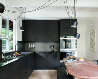 "The kitchen features hacked IKEA cabinets—Brit and Daniel built custom fronts and side panels out of Valchromat, a recycled engineered wood. The cabinets are topped with black steel, which extends up the wall as backsplash. ""We wanted to find an inexpensive way of doing a really terrific kitchen,"" says Daniel. ""The metal, which is a cold-rolled sheet of blackened steel, is a unique material that will develop a patina over time, but will also be super durable—and again, very cost effective."""