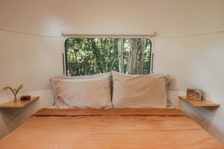 In the back of the trailer, a queen bed opens to storage underneath. Two floating shelves—installed in the trailer's rounded corners with pocket screws—serve as nightstands.