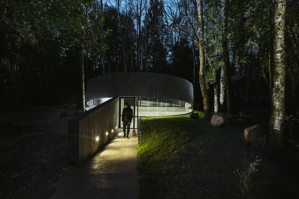 The structure is nestled into the earth and then slightly tilted upward to create an access portal.