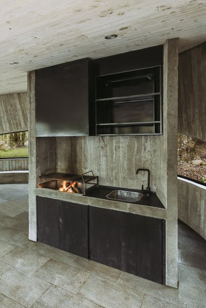 In the cooking area, an open fire is used for barbecuing.