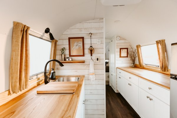 In the kitchen, birch cabinets painted in a bright white are topped with solid ash countertops.