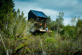 The two-story cabin runs solely off of solar power and rainwater.