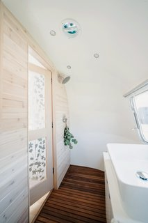 The bathroom walls are clad in whitewashed cedar.