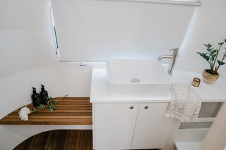 In the wet bath, a teak bench and flooring add warmth to the all-white space.