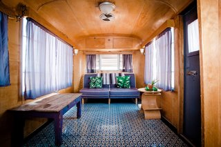 This vintage trailer near Taos, New Mexico, has a charming interior with wood-clad walls and a patterned floor.