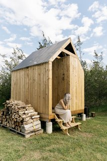 The wood-clad bathhouse, which holds a shower and composting toilet, is topped with a corrugated PVC roof.