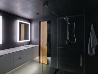 While most of the interior is clad in wood, the bathroom is covered in a sleek gray tile.