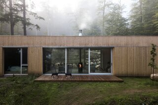 A rotating fireplace, a glazed facade, and a cozy sauna complete this wonderful woodland retreat.