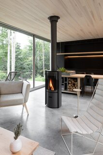 A rotating wood stove in the center of the open-concept living and dining area provides 360-degree access to the fire.