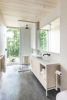 Concrete stretches across the bathroom floor into the shower, where a floor-to-ceiling window frames the great outdoors. A simple palette of concrete, plywood, and keystone white mosaic tile gives the bathroom a clean look.