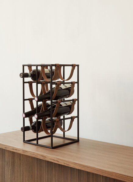 "Arthur Umanoff's wine rack was originally a design for Shaver-Howard Furniture. ""The wine rack was really popular and he made different versions of them—square ones, tall ones,"" says Wendy. ""I think those leather straps are a play on his last name. They are U-shaped, and they could've been done straight. I always felt that way."" The Umanoff black metal wine rack retails for $359.95 at MENU."