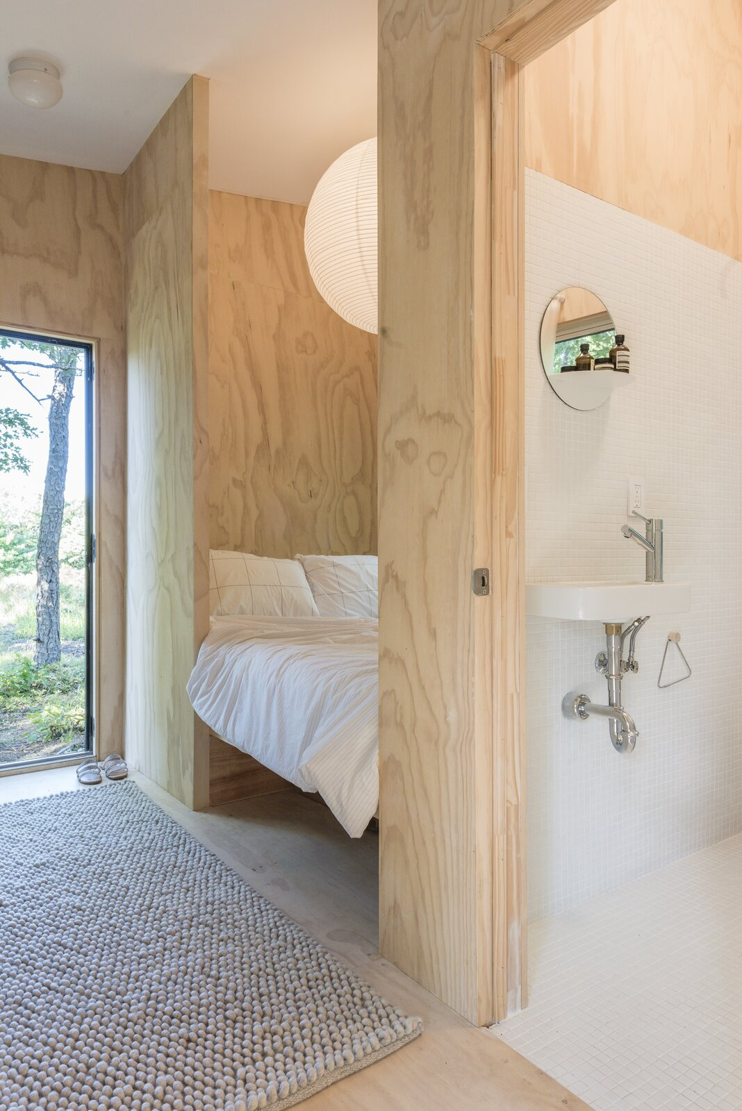 Bath Room, Ceiling Lighting, One Piece Toilet, Wall Mount Sink, Ceramic Tile Wall, and Ceramic Tile Floor A small yet full-sized bath houses a tub, compost toilet and sink.  Photo 6 of 10 in The Cofounders of Den, a DIY Cabin Startup, Share a Peek Into Their Catskills Retreat