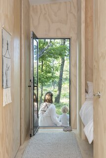 To maximize on communal living space, the couple went minimal with bunking space. Their queen-size bed is tucked in an alcove and a pocket door was created to tuck away a crib or twin bunks.