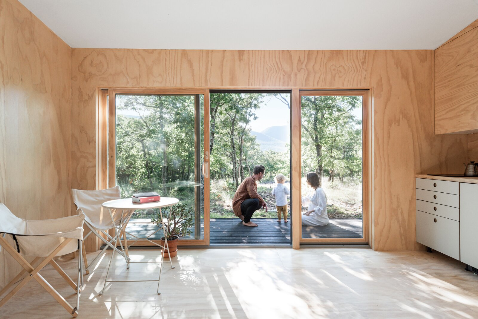 Living, Light Hardwood, Wood Burning, and Bar The family of three (soon to be four) uses the minimalist-inspired cabin in the Catskills as their peaceful weekend getaway. In the future they hope to build a larger home and turn the cabin into a guest house.  Living Bar Photos from The Cofounders of Den, a DIY Cabin Startup, Share a Peek Into Their Catskills Retreat