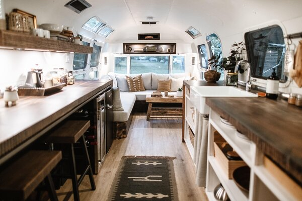 A neutral color scheme and wood elements give the trailer a cozy, rustic feel.