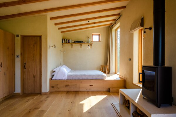 A wood sleeping berth with built-in storage helps to delineate the bedroom from the living area in the open-concept cabin.