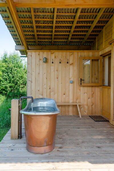 A copper tub on the larch veranda encourages al fresco living.