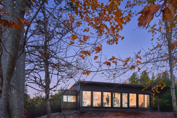 The 1,000-square-foot contemporary structure overlooks a nearby lake through floor-to-ceiling windows.